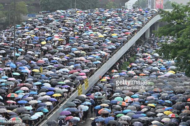 TOPSHOT Protesters shelter under umbrellas during a downpour as they occupy roads near the government headquarters in Hong Kong on June 12 2019 Tens...