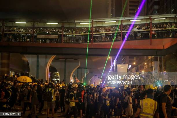 Protesters shine lasers towards the police during clashes following a march against a controversial extradition bill in Hong Kong on July 21 2019