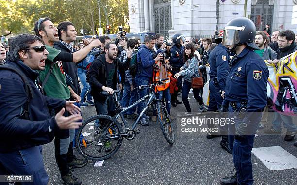 Protesters shout in front of riot policemen during a general strike in Madrid on November 14, 2012. General strikes in Spain and Portugal will...