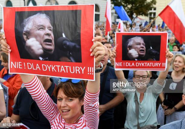 Protesters shout slogans and hold posters reading 'No to dictatorship' during a protest in front of the presidential palace in Warsaw as they urge...