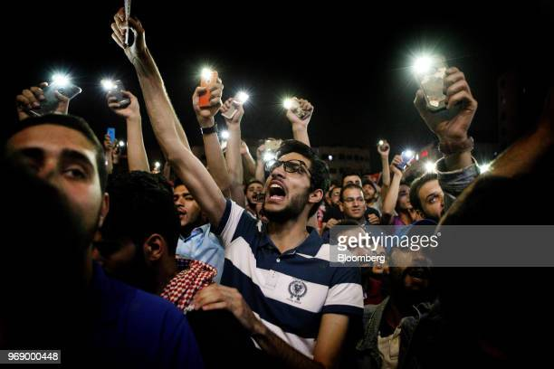 Protesters shout slogans and illuminate their mobile phones during a demonstration against a draft income tax law near the prime minister's office in...