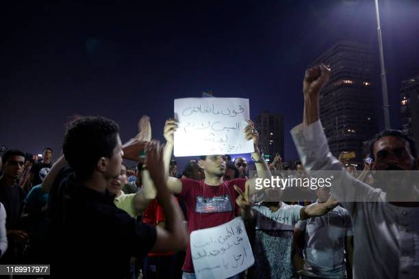 Protesters shout slogans and raise signs as they take part in a protest calling for the removal of President Abdel Fattah al-Sisi, along the October...