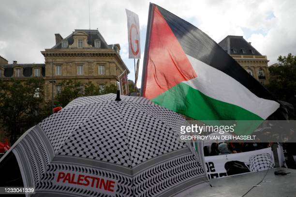 Protesters shout slogans and wave Palestinian flags during a demonstration in solidarity with the Palestinian people on Republique square in Paris on...