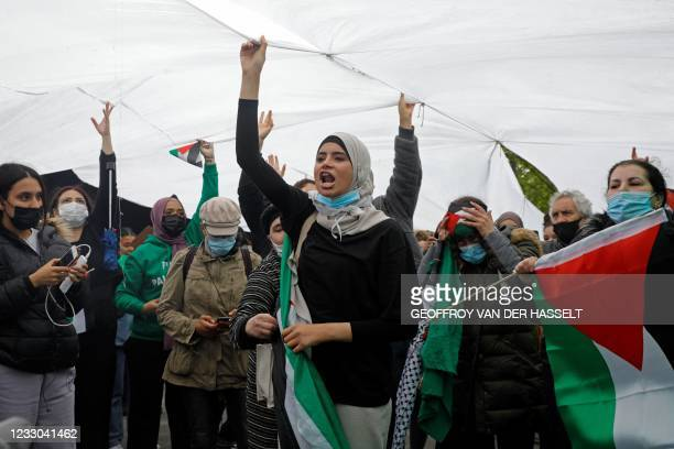 Protesters shout slogans and wave Palestinian flags during a demonstration in solidarity with the Palestinian people, in Paris on May 22, 2021. - The...
