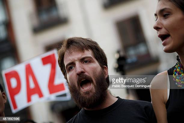 Protesters shout slogans as a placard reads 'Peace' during a demonstration to show solidarity and support for refugees on September 12 2015 in Madrid...