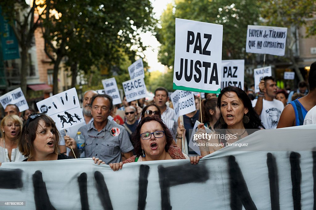 Protesters shout slogans as a woman (R) holds a placard reading 'Just peace' during a demonstration to show solidarity and support for refugees on September 12, 2015 in Madrid, Spain. Several cities across Spain have called for demonstrations under the slogan 'Welcome refugees. For a more responsible European policy'. Europe is facing the region's largest crisis of migrants and refugees since World War II. Spain would have to take nearly 15,000 refugees under a new European Union plan to relocate 120,000 refugees. Many Spanish cities and citizens took the lead on offering their support to refugees.