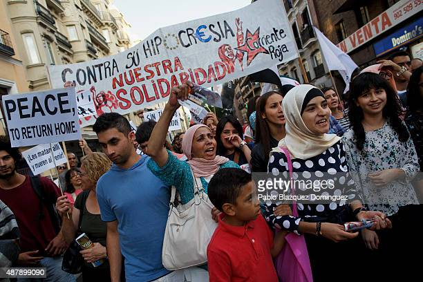 Protesters shout slogans as they hold a placard reading 'Peace then return home' and a banner 'Against their hipocrisy our solidarity Red tide'...