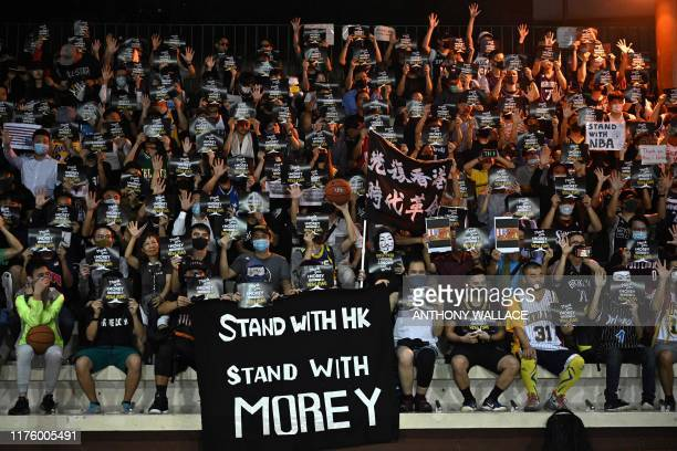 Protesters shout slogans as they hold flyers at the Southorn Playground in Hong Kong on October 15 during a rally in support of NBA basketball...