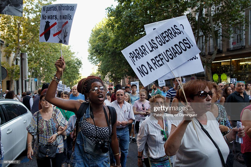 Protesters shout slogans as they hold placards reading 'No wars, no walls' (L) and 'Stop wars, not refugees!' (R) during a demonstration to show solidarity and support for refugees on September 12, 2015 in Madrid, Spain. Several cities across Spain have called for demonstrations under the slogan 'Welcome refugees. For a more responsible European policy'. Europe is facing the region's largest crisis of migrants and refugees since World War II. Spain would have to take nearly 15,000 refugees under a new European Union plan to relocate 120,000 refugees. Many Spanish cities and citizens took the lead on offering their support to refugees.
