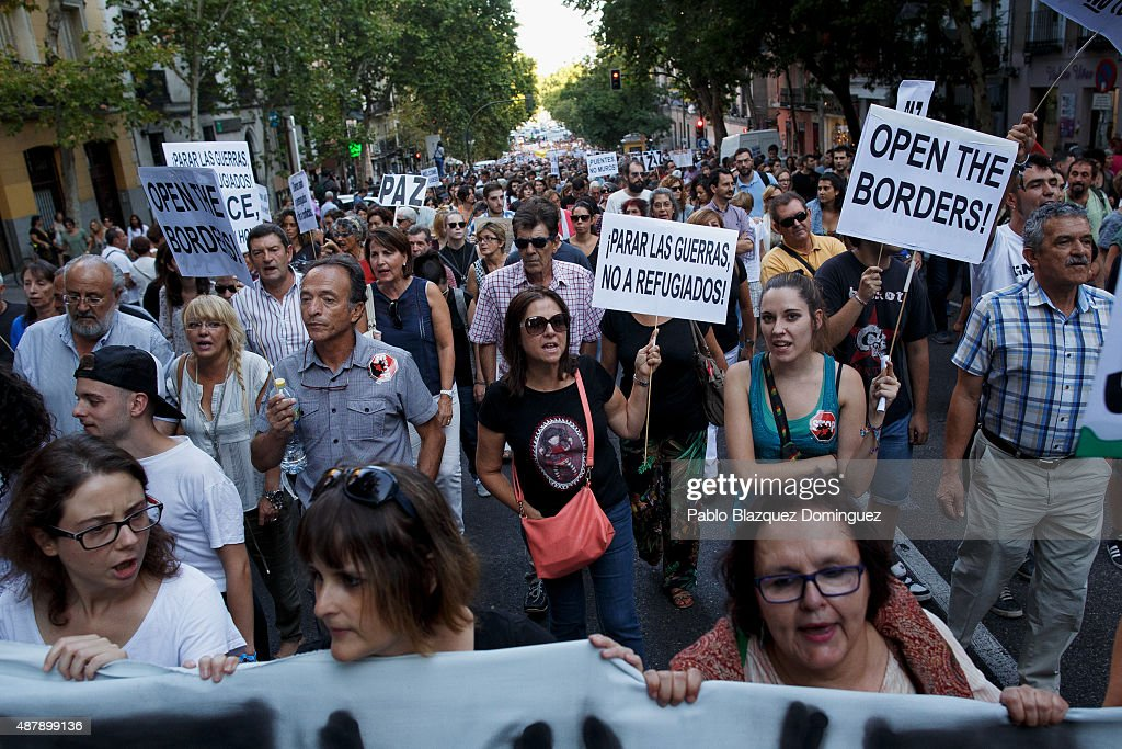 Protesters shout slogans as they hold placards reading 'Open the borders' (R) and 'Stop wars, not refugees!' (C) during a demonstration to show solidarity and support for refugees on September 12, 2015 in Madrid, Spain. Several cities across Spain have called for demonstrations under the slogan 'Welcome refugees. For a more responsible European policy'. Europe is facing the region's largest crisis of migrants and refugees since World War II. Spain would have to take nearly 15,000 refugees under a new European Union plan to relocate 120,000 refugees. Many Spanish cities and citizens took the lead on offering their support to refugees.