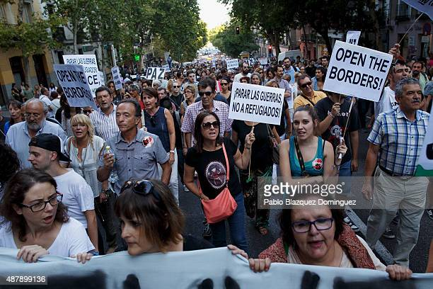 Protesters shout slogans as they hold placards reading 'Open the borders' and 'Stop wars not refugees' during a demonstration to show solidarity and...