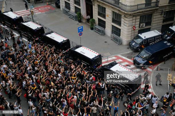 Protesters shout slogans during a demonstration outside the Spanish national police headquarters in Barcelona on October 2 2017 to protest against...