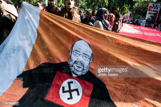 Protesters shout slogans next to a large caricature of Indian Home Minister Amit Shah with a Nazi Party swastika symbol during a demonstration...