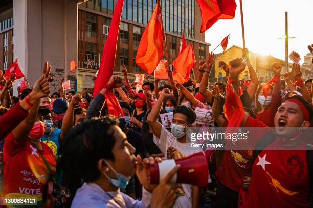 Protesters shout slogans while carrying red flags on February 07, 2021 in downtown Yangon, Myanmar. Some internet services were restored in Myanmar...