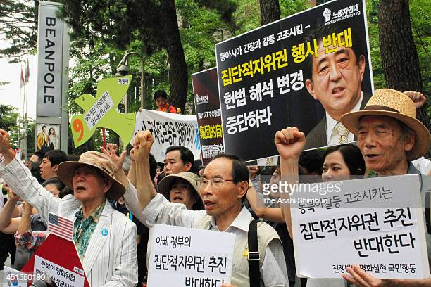 Protesters shout their opposition to the Abe Cabinet's move to allow Japan to exercise the right to collective selfdefense on July 1 2014 in Seoul...