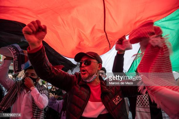 Protesters shouting under a large Palestinian flag during a demonstration against the last attacks by Israel to Palestinian people and coinciding...
