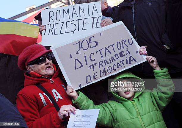 Protesters shouts antigovernmental and hold banners reading in Romanian Wakeup Romania Down with the Dictator Live the Democracy during a protest to...