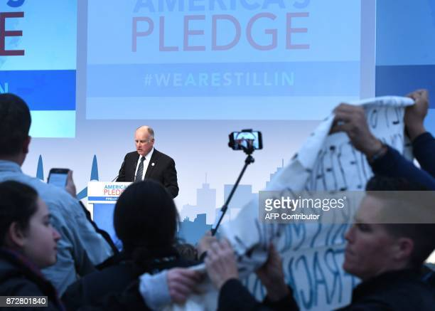 Protesters show banners and protest during the speech of US Governor of California Jerry Brown at the launch event at the US climate action center on...