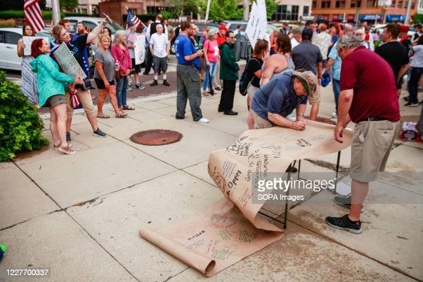 Protesters sign a banner to be left on the doors of the Statehouse during the We Will Not Comply anti mask rally. People protest against both the...