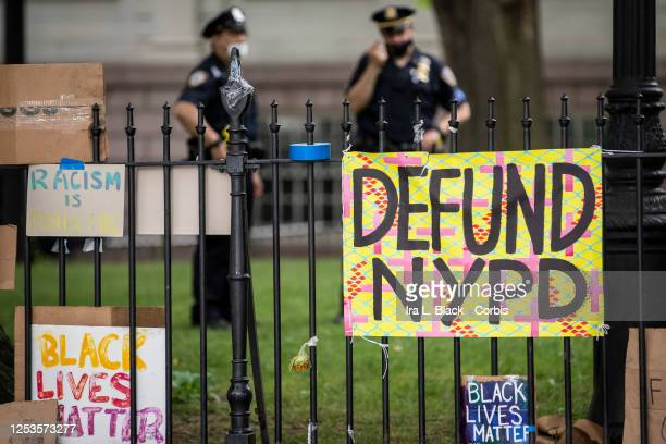 """Protesters signs hang on the gate in City Hall Park during the Occupy City Hall protests that say, """"Defund NYPD"""" and """"BLM"""" with NYPD police officers..."""