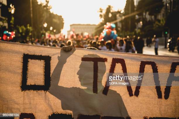 A protester's silhouette behind banners while shouting slogans during a demonstration to mark the 103rd anniversary of the Armenian Genocide by...