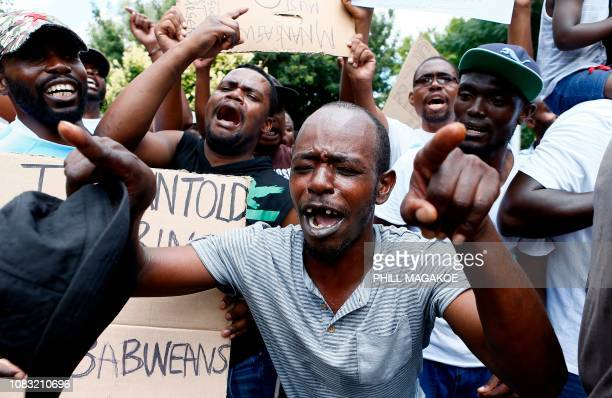 TOPSHOT Protesters sing during a demonstration of Zimbabwean citizens outside the Zimbabwean Embassy in Pretoria on January 16 following the...
