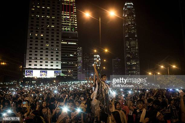 Protesters sing songs and wave their cell phones in the air after a massive thunderstorm passed over outside the Hong Kong Government Complex on...