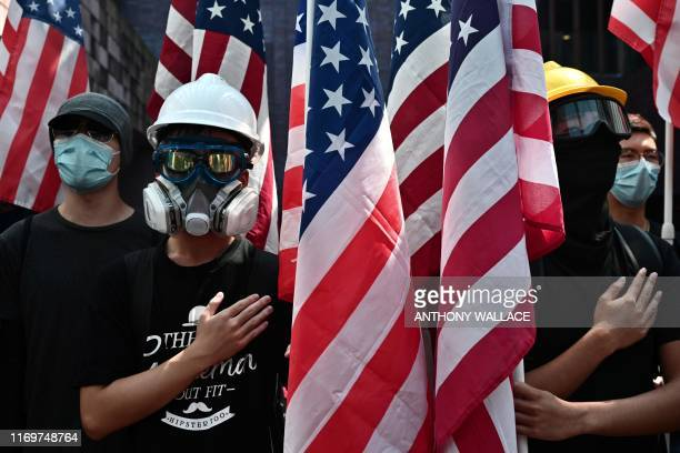 Protesters sing the StarSpangled Banner as they march while holding the US flag at the Hong Kong University campus on September 20 as they rally for...