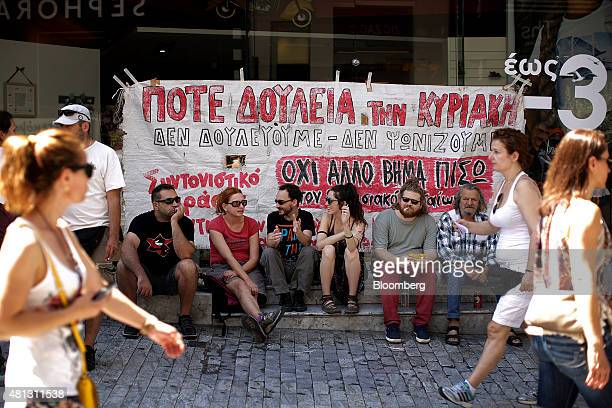Protesters sit in front of a banner taped to the front of a clothing store to demonstrate against stores opening and trading on Sundays in Athens...