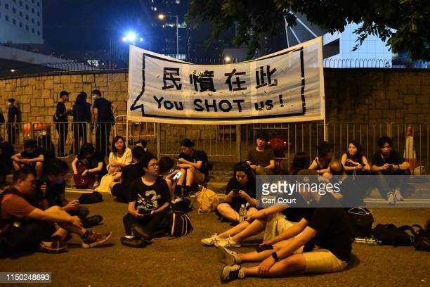 Protesters sit in the road next a a banner as they demonstrate near the Legislative Council building against the nowsuspended extradition bill on...