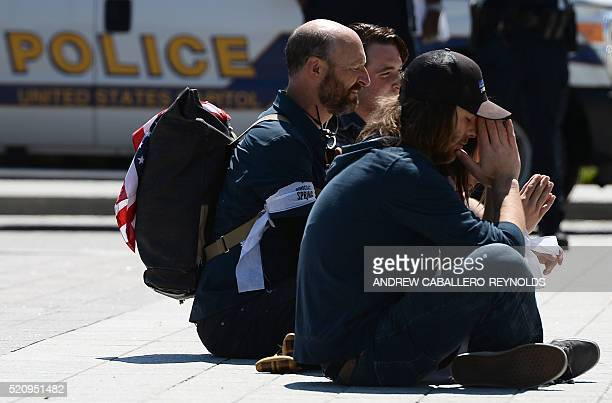 Protesters sit on the ground as they wait to be arrested during a Democracy Spring demonstration on Capitol Hill in Washington DC on April 13 calling...