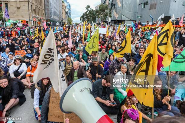 Protesters sit on the ground on a major road in the centre of the city to mark the beginning of the Extinction Rebellion protests in Melbourne on...