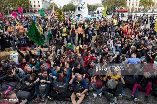 Protesters sit on the ground to block the Pont au Change bridge during a demonstration called by climate change activist group Extinction Rebellion...