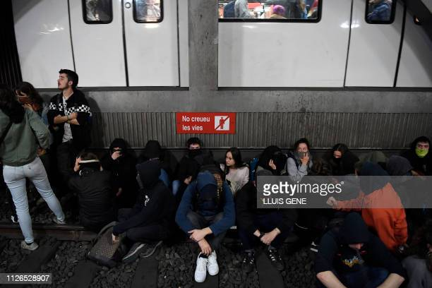Protesters sit on the railroad tracks after occupying a train station in Barcelona during a strike day against the trial of former Catalan separatist...