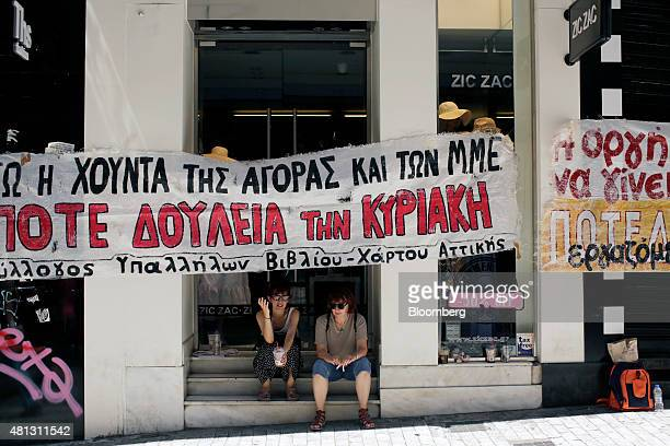 Protesters sit underneath a banner pinned across the front of a clothing store to demonstrate against stores opening and trading on Sundays in Athens...