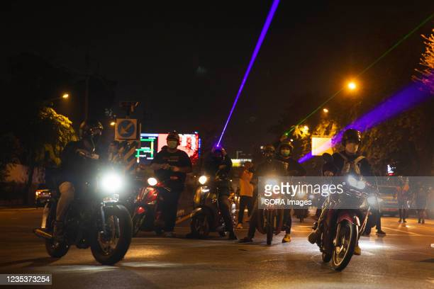 Protesters sitting on motorcycles point lasers at the riot police during the demonstration. The pro-democracy protesters gathered at democracy...