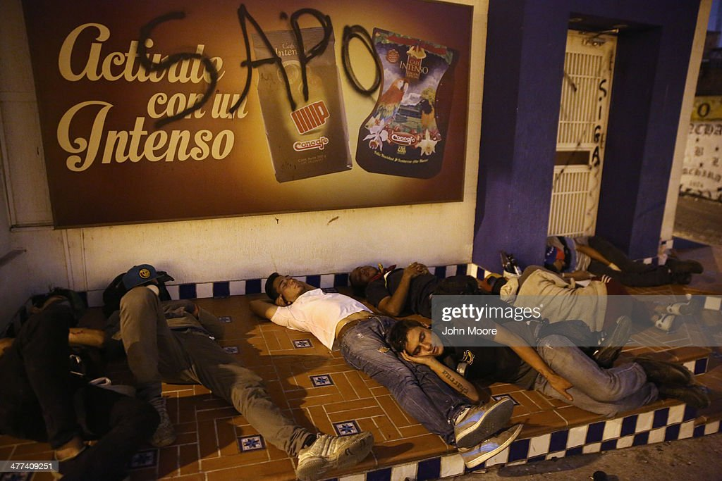 Protesters sleep before their shift manning a barricade before dawn on March 9, 2014 in San Cristobal, the capital of Tachira state, Venezuela. Local residents have manned barricades throughout the nights, skirmishing with security forces for almost a month, while protesting against the federal government. Tachira, which borders Colombia, has been a focal point for anti-government protests nationwide.