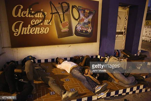 Protesters sleep before their shift manning a barricade before dawn on March 9 2014 in San Cristobal the capital of Tachira state Venezuela Local...
