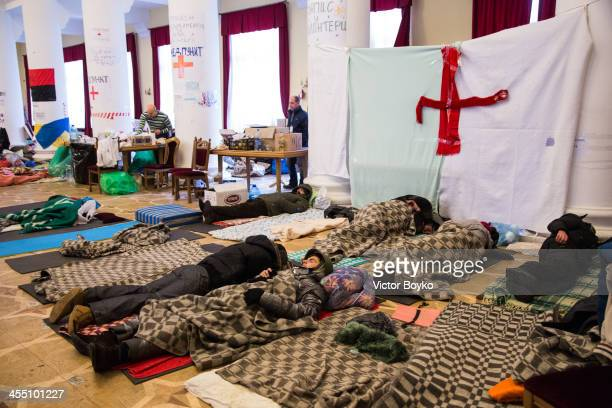 Protesters sleep in the pillar hall of the City Hall after the riot police were forced out from blocking the front door as authorities launched an...