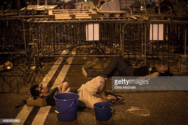 Protesters sleep in the street next to a makeshift barricade in the early hours of the morning outside the Hong Kong Government Complex on September...