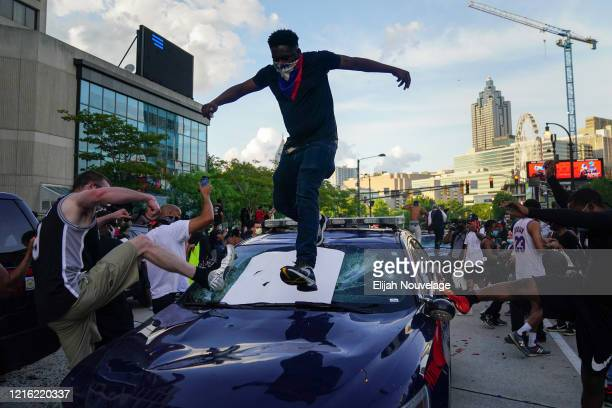 Protesters smash a police car during a protest on May 29 2020 in Atlanta Georgia Demonstrations are being held across the US after George Floyd died...