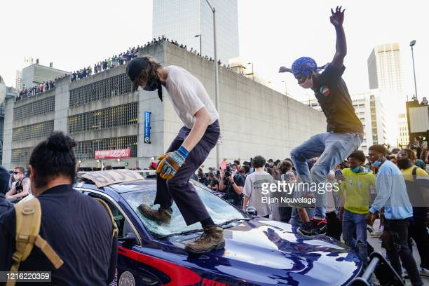 Protesters smash a police car during a protest outside CNN Center on May 29 2020 in Atlanta Georgia Demonstrations are being held across the US after...