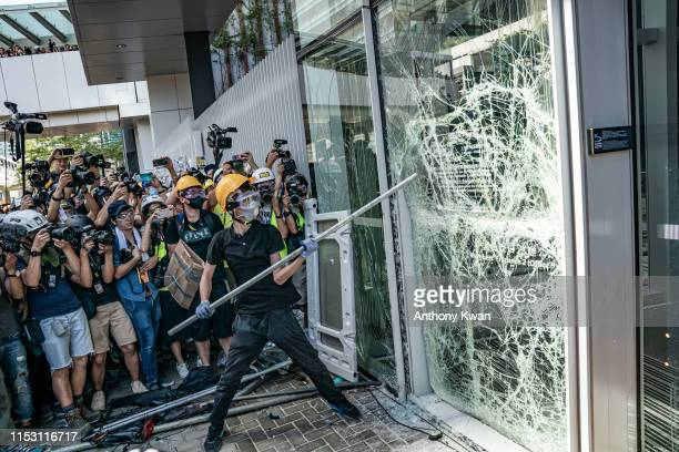 Protesters smash glass doors and windows of the Legislative Council Complex on July 1 2019 in Hong Kong China Antiextradition protesters attempts to...
