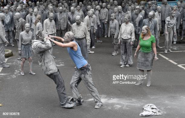 Protesters smeared with clay demonstrate during the art action '1000 Gestalten' on July 5 2017 in Hamburg northern Germany where leaders of the...