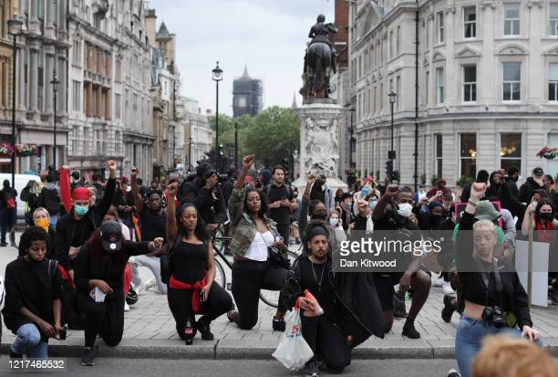 Protesters some wearing face masks take the knee and raise clenched fists during a Black Lives Matter protest in Trafalgar Square on June 3 2020 in...