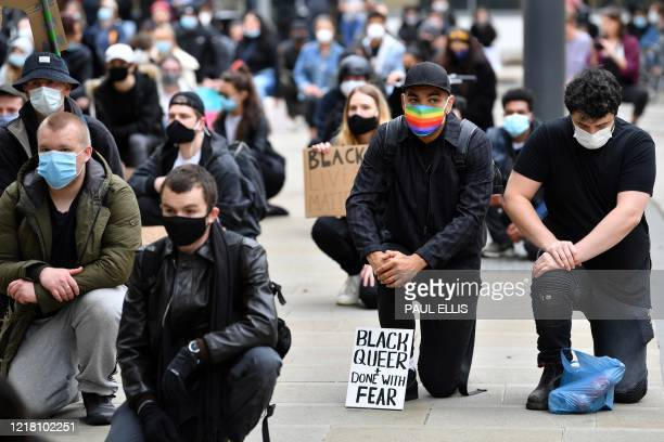 Protesters some wearing PPE including a face mask as a precautionary measure against COVID19 hold placards as they attend a demonstration in...