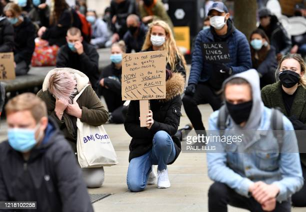 Protesters ,some wearing PPE , including a face mask as a precautionary measure against COVID-19, hold placards as they attend a demonstration in...