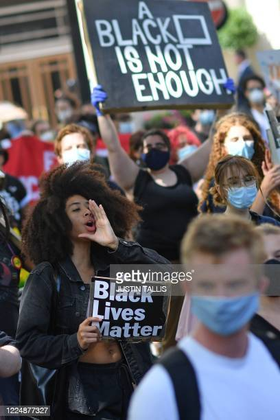 Protesters, some wearing protective face coverings hold placards as they march down Park Lane in support of the Black Lives Matter movement in London...