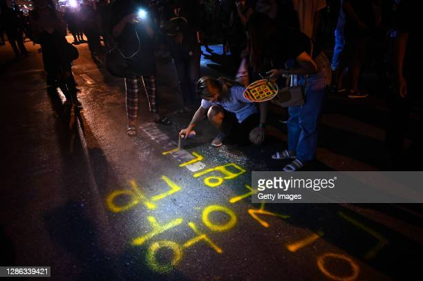 Protesters spray paint graffiti in Korean language at the Ratchaprasong Intersection on November 18, 2020 in Bangkok, Thailand. Pro-democracy...