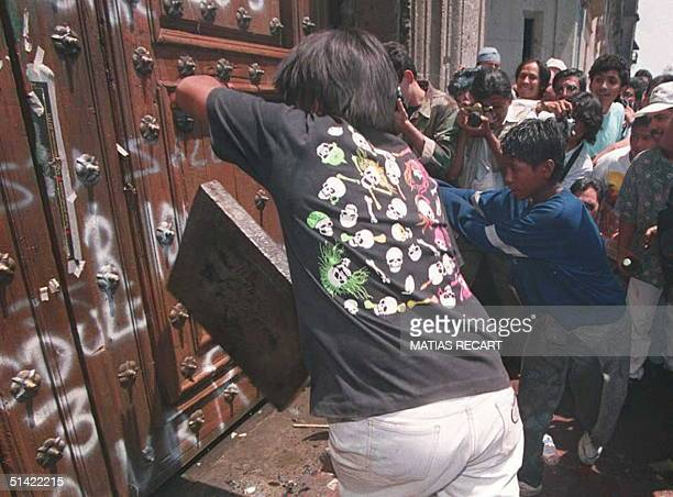 Protesters spray paint the doors of the National Palace with graffiti in Mexico City 01 May during May Day demonstrations Tens of thousands of...